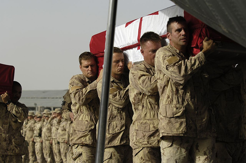 Coalition Forces gather on the Airfield in Kandahar, Afghanistan, July 26, 2006 to pay their respects as the remains of Corporal Francisco Gomez, 44, Princess Patricia's Canadian Light Infantry in Edmonton and Cpl Jason Patrick Warren, 29, a reservist with the Black Watch, Royal Highland Regiment of Canada in Montreal, are carried into a CC-130 Hercules for Repatriation to Canada. Photo by MCpl Robert Bottrill, Canadian Forces Combat Camera.