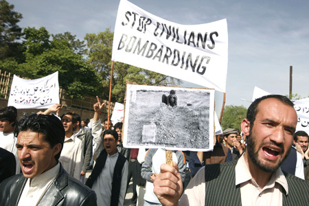 Students of Kabul University, one holding a photo showing graves of Afghan victims killed in airstrikes, shout anti-U.S. slogans during a demonstration against coalition airstrikes in Farah in May, 2009. Photo: Sadeq/AP.