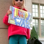 September 12, 2013: The youngest member of an information picket outside the Fort Garry Hotel in Winnipeg, denouncing Lloyd Axworthy's call for war with Syria. Photo: Paul S. Graham